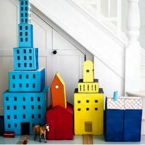 Juntando alguns rolinhos de papel, tinta, papelão, cola, fita adesiva e tesoura para montar uma cidade em miniatura com a criançada.